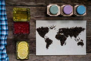 map of the world, lined with tea leaves on old paper. Eurasia, America, Australia, Africa. vintage. tea, a towel, honey, raspberry jam with lemon on rustic wooden table. top view. flat lay